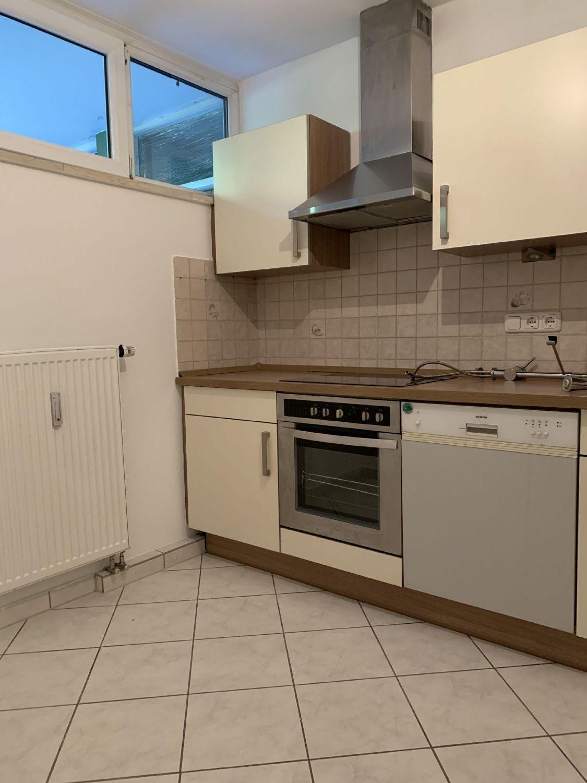 Einbauküche mit Fenster, und hellen Bodenfliesen